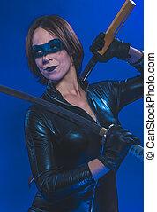 brunett, flicka, klätt, in, läder, och, latex, inpassat, med, japansk, svärd, på, blåttbakgrund