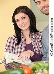 brunette and man in kitchen preparing recipe