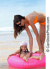 brunette at the beach with child