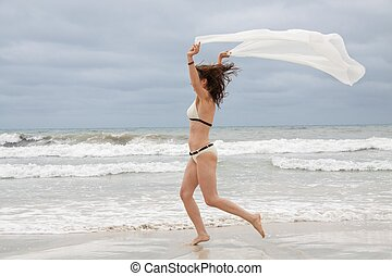 brunette attractive woman carefree on beach summer freedom