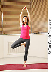 Brunette balancing on one leg yoga pose