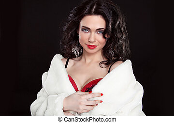 Brunette beautiful girl posing in fur coat over dark