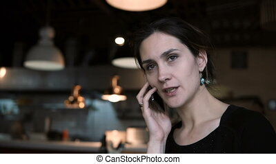 Brunette beautiful woman sitting in cafe and talking on mobile phone with friends. Attractive female using smartphone.