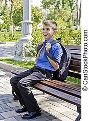 Brunette boy sitting on bench with school backpack