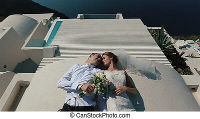 Brunette bride and groom lying and smiling on the terrace in white dress with sea background