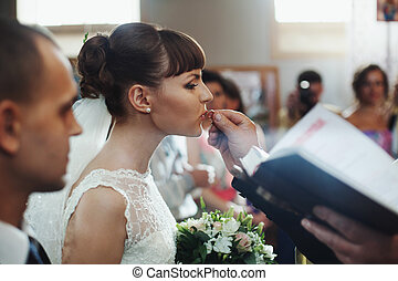 Brunette bride kisses a delicate wedding ring held by a priest
