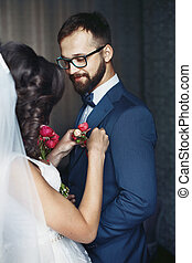 Brunette bride putting on flower boutonniere on happy groom in blue suit