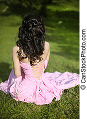 Brunette bride resting and sitting on green grass at spring park. beauty portrait.