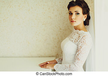 Brunette bride stands straight at a white wall