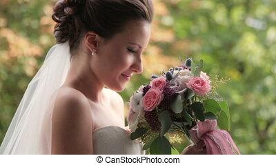 Brunette bride with wedding bouquet on green background
