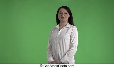 Brunette business woman in white shirt talking against a green screen