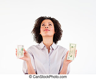 Brunette businesswoman holding dollars and looking upwards -...