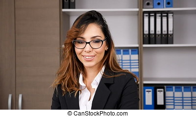 Brunette businesswoman in office smiling at the camera