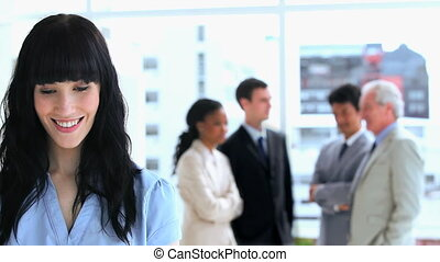 Brunette businesswoman standing in front of her team