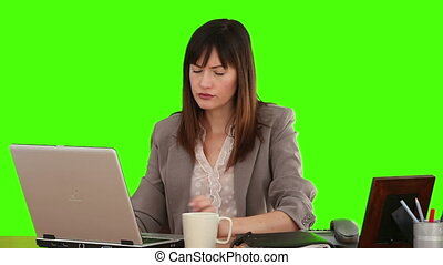 Brunette businesswoman working while she is holding a cup of tea against a green screen
