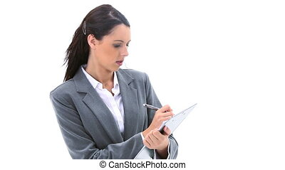 Brunette businesswoman writing on a clipboard