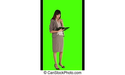 Brunette businesswoman writing something on her diary