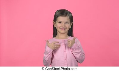Brunette child smiling and show thumbs up on pink...