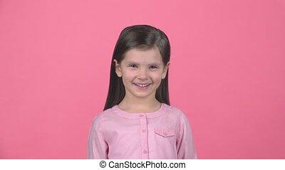 Brunette child smiling on pink background. Slow motion