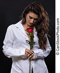 Brunette curly woman with red rose