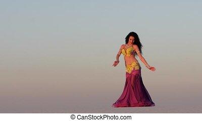 Brunette dances belly dancing in the sandy desert, her...