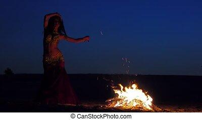 Brunette dancing belly dance near the fire, against a...