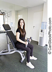 Brunette do exercise with dumbbells in gym - Brunette with...