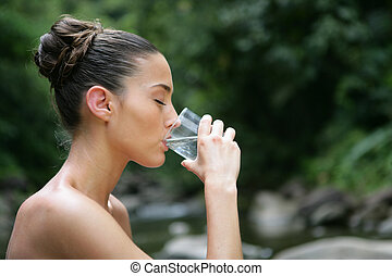 Brunette drinking a glass of water outdoors