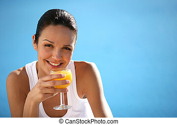 Brunette drinking fruit juice by swimming pool
