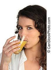 Brunette drinking glass of juice