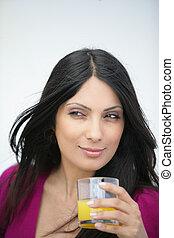 Brunette drinking orange juice