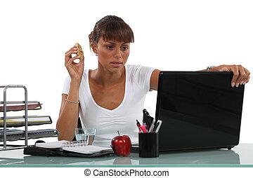 Brunette eating at her desk