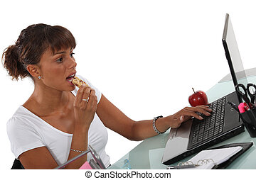Brunette eating snack at her desk