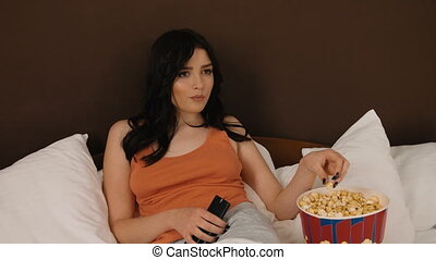 Brunette eating tasty popcorn and watching TV at home.