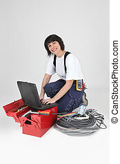 brunette electrician with miscellaneous tools looking happy