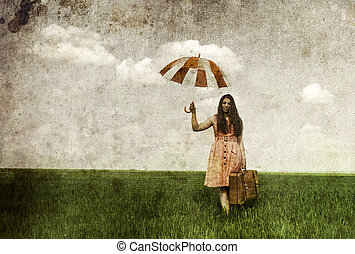 Brunette enchantress with umbrella and suitcase at spring rapeseed field. Photo in old image style.