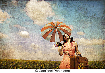 Brunette enchantress with umbrella and suitcase