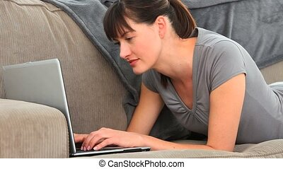 Brunette enjoying a chat on a laptop