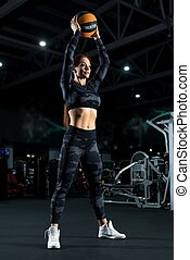 Brunette exercising with a ball in a gym shot