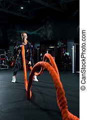 Brunette exercising with a rope in a gym shot