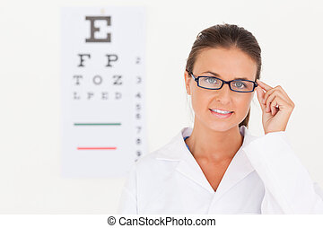 Brunette eye specialist wearing glasses looking into the camera