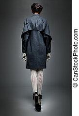 Brunette fashion model in grey coat backwards view