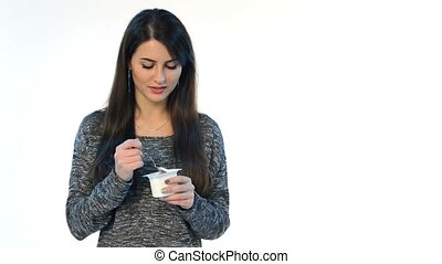 Brunette female eating yoghurt