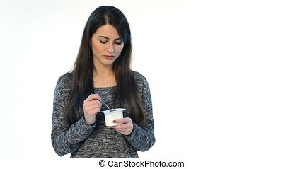 Brunette female eating yoghurt, studio shot over white...