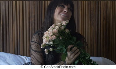 Brunette female holding bouquet of roses