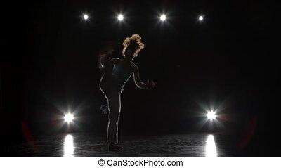Brunette female practicing capoeira in darkness against...