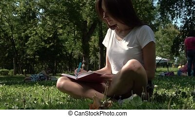 Brunette Female Sitting in Park with Notebook
