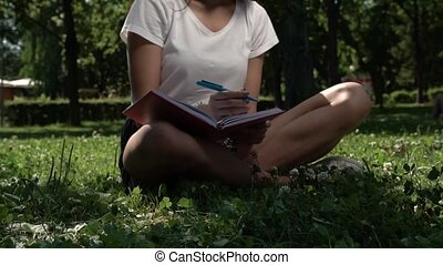 Brunette Female Sitting in Park with Notebook - Brunette...