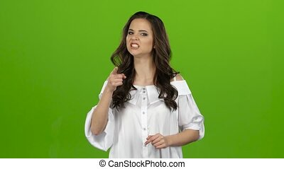 Brunette girl is very angry and screams, she is excited and nervous. Green screen