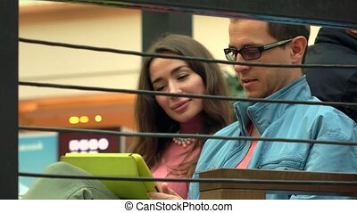 Brunette girl and man in glasses using tablet computer together in a cafe. 4K shot